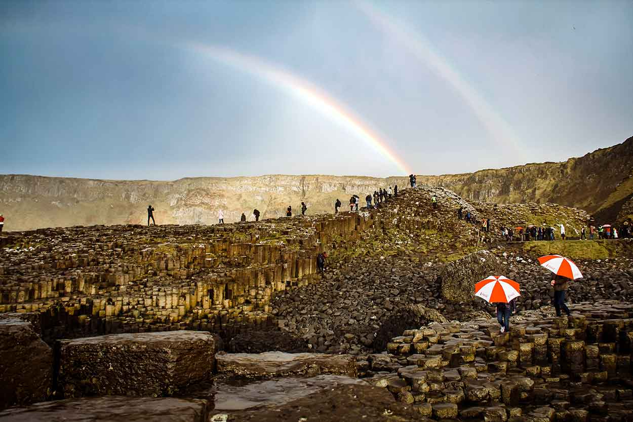 people with umbrellas on giants causeway